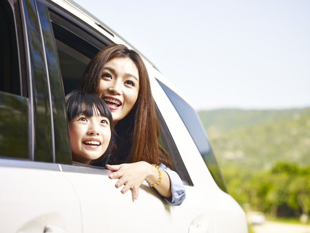 young asian mother and daughter sticking their heads out of rear window while riding in a car. Stock Photo