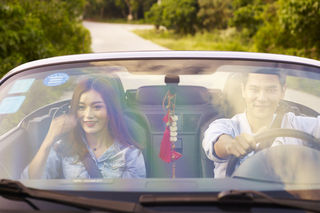 rich life: young asian couple enjoying a ride in a convertible sports car.