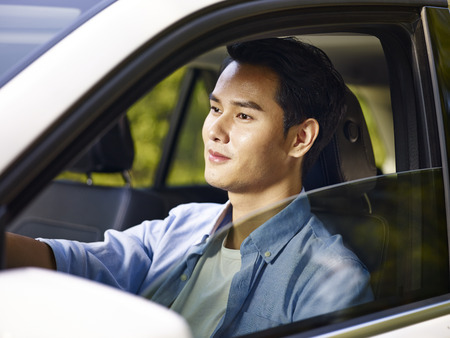 young asian man driving a car, happy and smiling.