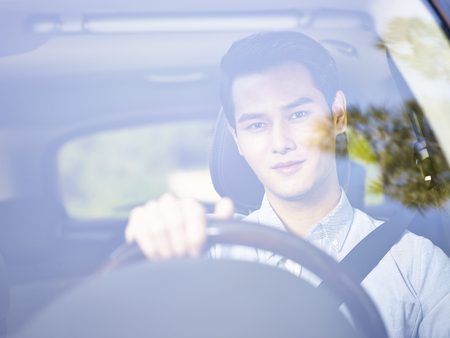 young asian man driving a vehicle seen through the windshield glass.