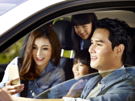 gelukkige Aziatische familie met twee kinderen reizen met de auto, moeder met behulp van mobiele telefoon terwijl vader rijden, focus op de vader. Stockfoto