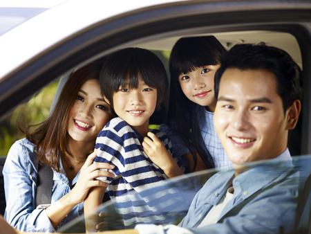 gelukkige Aziatische familie met twee kinderen die reizen met de auto, focus op de kleine jongen. Stockfoto