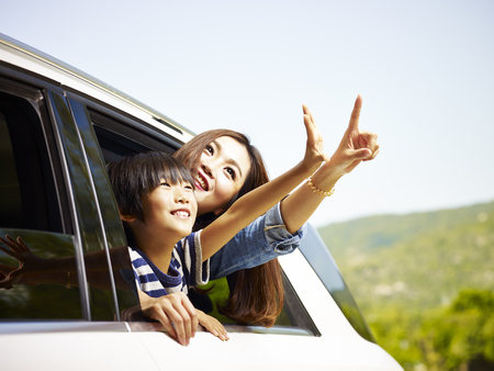 happy asian mother and son sticking heads out of rear window of a car looking at scenery. Stock Photo