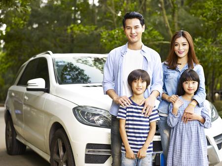 車で旅行中に写真を撮る二人の子供を持つアジア系の家族。