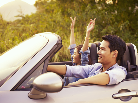 young asian couple riding in a convertible sport car enjoying the cool breeze at sunset.
