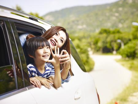 gelukkige Aziatische moeder en zoon stekende hoofden uit achterruit van een auto die landschap bekijken.