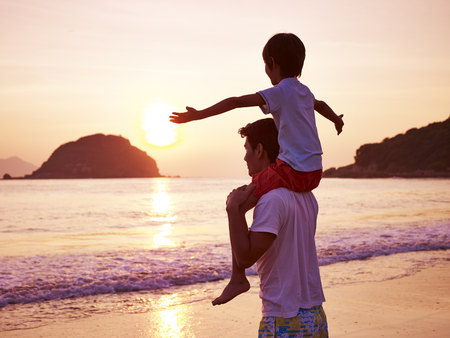 young asian father carrying son on shoulder on beach at sunrise. 版權商用圖片 - 77134110