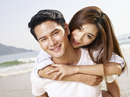 young asian man carrying girlfriend or wife on back on beach. Banque d'images