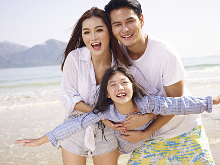 young asian couple carrying daughter having fun on beach. Stock Photo