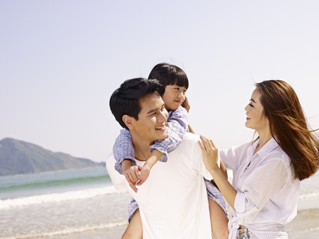 happy asian family having fun on beach.