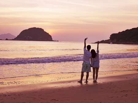 woman sunset: young asian couple taking a walk on beautiful beach before sunrise.