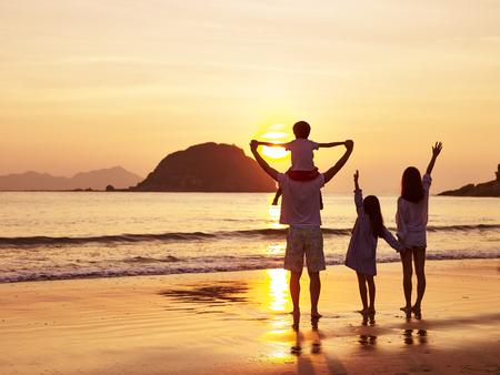 아시아 가족보고 및 일출 또는 일몰 즐기는 해변에 서 서.