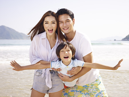 man flying: young asian couple carrying daughter having fun on beach. Stock Photo