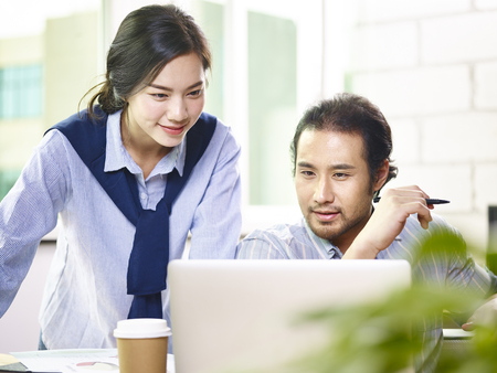 asian business teammates working together in office using laptop with a smile on face.