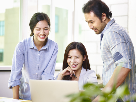 a team of young and cheerful asian business executives working together in office using laptop computer. Stock Photo