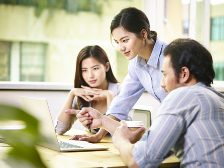 een team van jonge Aziatische corporate executives bespreken zaken in kantoor met behulp van laptop computer.