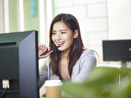 젊은 아시아 사업가 컴퓨터를 사용하는 사무실에서 작업합니다. 스톡 콘텐츠