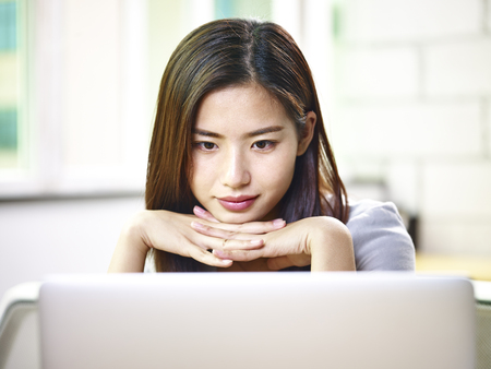 young asian businesswoman working in office using laptop computer. Banque d'images