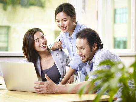 Giovane squadra di affari asiatici team lavorando insieme in ufficio utilizzando computer portatile.