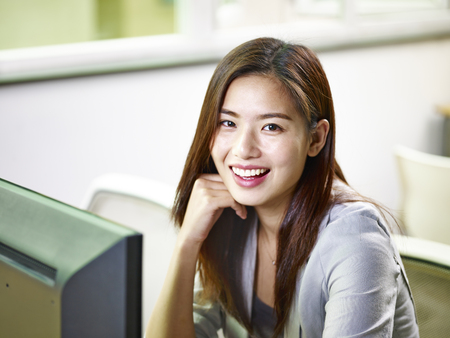 young asian businesswoman working in office looking at camera smiling. Banque d'images