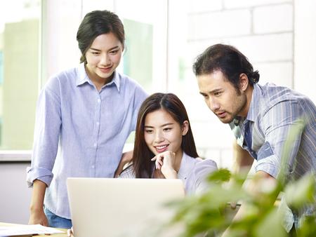 ラップトップ コンピューターを使用してオフィスで働く若いアジア ビジネス人々。