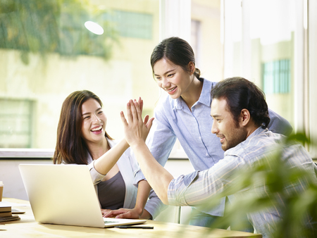 young asian business person giving coworker high five in office celebrating achievement and success.