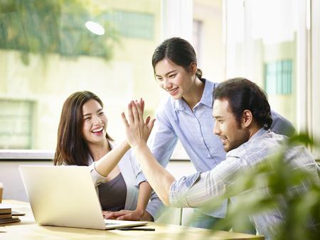 joven empresario asiático dando compañero de trabajo de alto cinco en la celebración de la oficina logro y el éxito.
