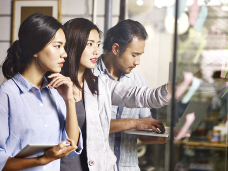 ラップトップ コンピューターと付箋を使った戦略ワーク ショップで一緒に働く若いアジア ビジネス人々。