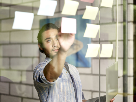 asian business man conducting an analysis in office using sticky notes.