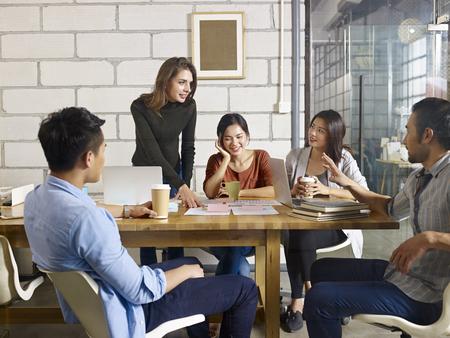 유리 회의실에서 비즈니스를 논의하는 다국적 사람들의 팀.