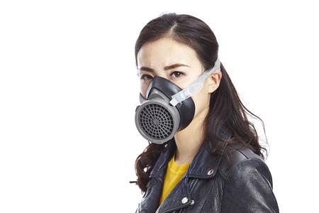 흰색 배경에 고립 된 카메라를 응시하는 가스 마스크를 쓰고 검은 가죽에 젊은 아시아 여자.