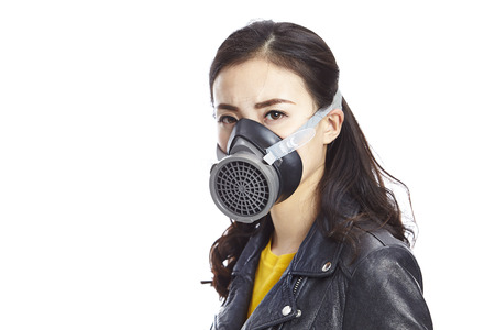 young asian woman in black leather wearing gas mask staring at camera, isolated on white background.