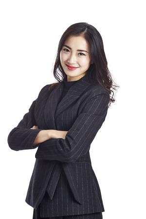 studio portret van een jonge Aziatische zakenvrouw in formele slijtage, armen gekruist, geïsoleerd op een witte achtergrond.