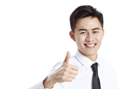 young asian businessman showing thumb-up sign, happy and smiling, studio shot, isolated on white background. Stock Photo