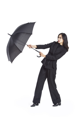 young asian businesswoman holding a black umbrella, studio shot, isolated on white background.