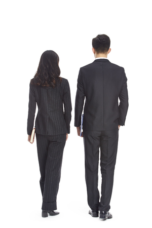 young asian business man and woman walking, rear view, isolated on white background. Stock Photo