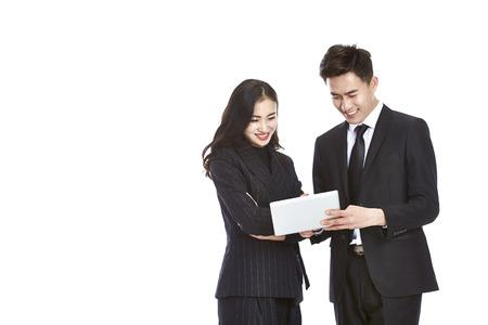 젊은 아시아 사업가 및 흰색 배경에 격리 된 미니 디지털 태블릿을 사용하여 함께 작동하는 사업가. 스톡 콘텐츠