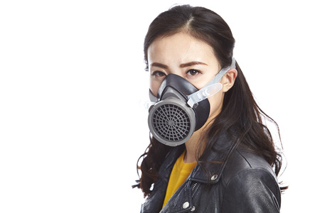 young asian woman in black leather jacket wearing a gas mask looking at camera, isolated on white background.