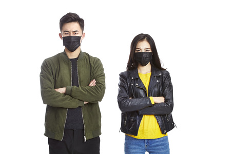 young asian man and woman wearing black mask looking at camera frowning, isolated on white background. Stock Photo
