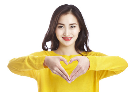 young and beautiful asian woman showing a heart shape formed with her hands, isolated on white background.