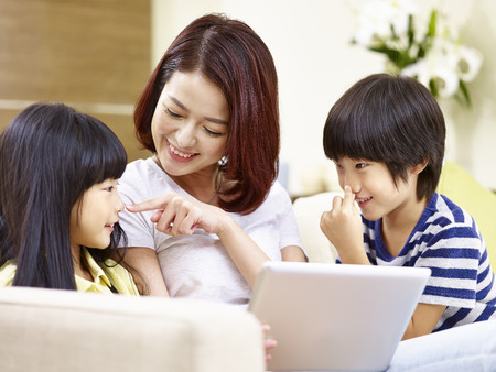 young asian mother sitting on couch at home having fun playing with son and daughter.