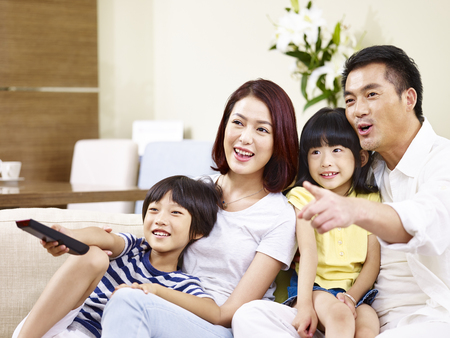 happy asian family with two children sitting on sofa watching TV together. Stock Photo