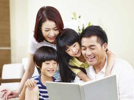 happy asian family with two children sitting on sofa reading a book together. Stock Photo