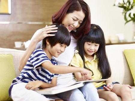 젊은 아시아 어머니와 함께 집에서 소파에 앉아, 책을 읽고, 행복하고 웃는 아이들.