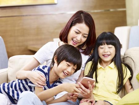 若いアジアの母と 2 人の子供が携帯電話を使用してホーム ゲームでソファに座っています。