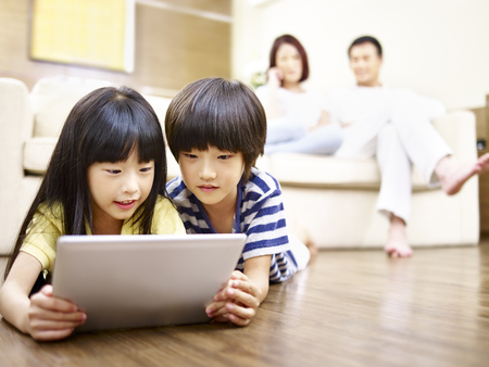 two asian children lying on floor playing video game using digital tablet while parents watching in the background.