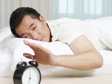 日本: asian man lying in bed trying to stop ringing alarm clock.