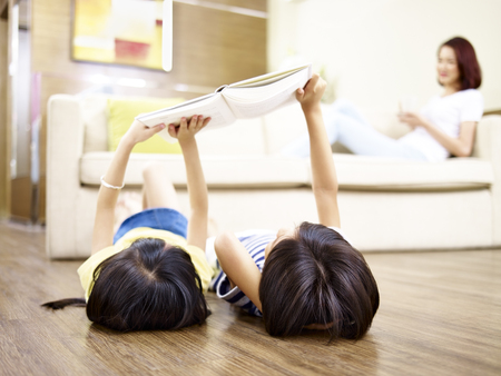 asian children lying on back on floor using digital tablet with mother sitting on couch in the background.