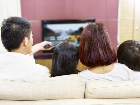 asian family sitting on couch at home watching TV, rear view. Stockfoto