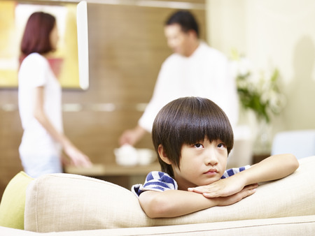 argue kid: asian child appears sad and unhappy while parents quarreling in the background. Stock Photo